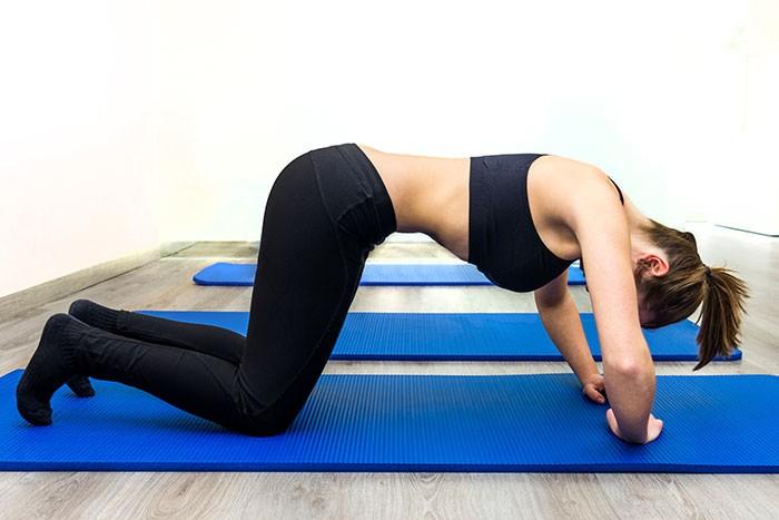 Mujer haciendo ejercicios para fortalecer el suelo pélvico.