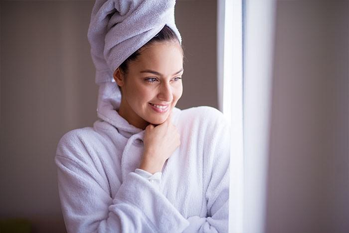 Mujer que lleva puesta una bata con una toalla en la cabeza.