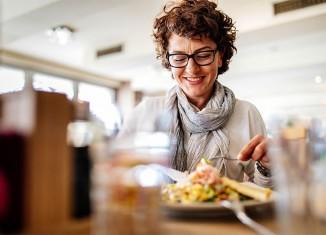 Mujer comiendo en un restaurante.