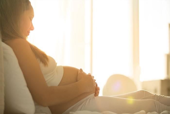 Mujer embarazada en la cama