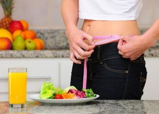 Mujer comiendo una ensalada midiendose la tripa