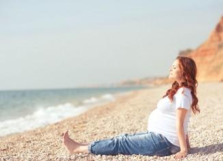 Mujer embarazada reposando en la playa