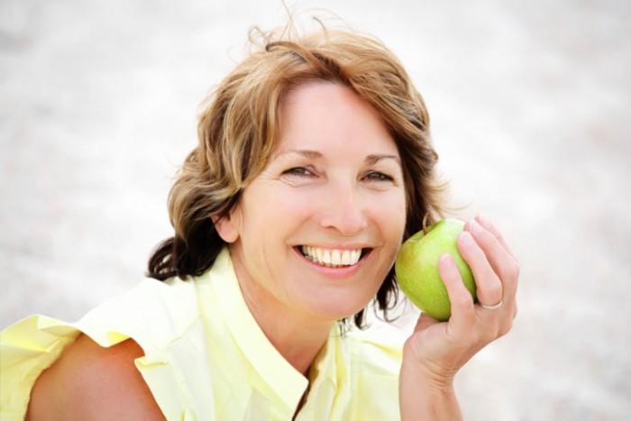 Mujer madura comiendo una manzana