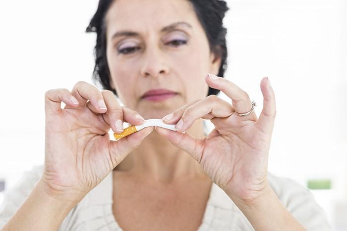 mujer madura rompiendo cigarrillo