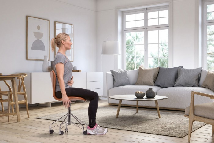 Mujer ejercitando su suelo pélvico sobre una silla
