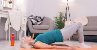 Mujer madura ejercitando su suelo pélvico en el salón de su casa