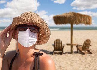 Mujer con mascarilla en la playa