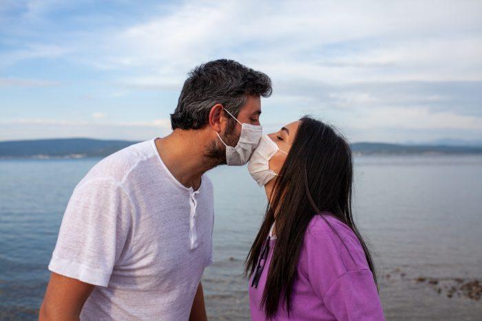 pareja besándose con mascarilla